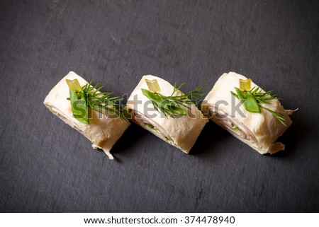 Small rolls with ham, cheese and pita on skewer on a black slate plate. Toned. - stock photo