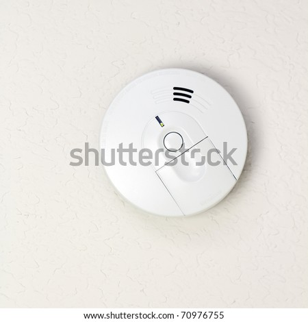 Small round battery operated device to warn residents of fire. - stock photo