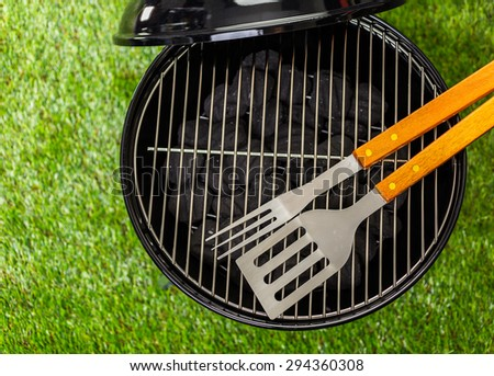 Small round charcoal grill ready for grilling at the summer picnic. - stock photo