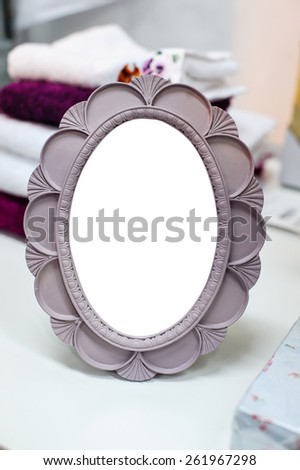 Small round mirror in a frame is on the table - stock photo