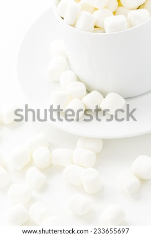 Small round white marshmallows on a white backgrouns.