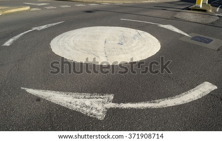 Small roundabout with white arrows - stock photo