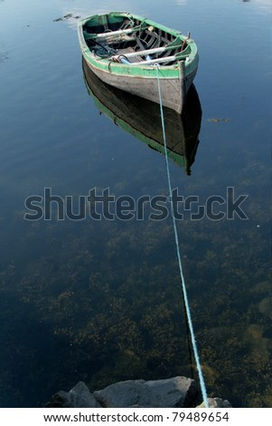 Small rowboat on a lake tied to the shore - stock photo