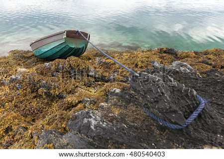 Small rowing boat laying on dry ground on rocks covered by seaweed, after sea level has fallen at low tide. Photographed at Norwegian coast, Helgeland.