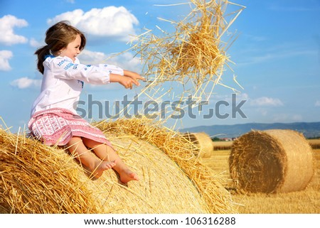 small rural girl on harvest field with straw bales - stock photo