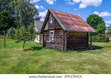 Small rural rustic brown house standing in a garden lawn - stock photo