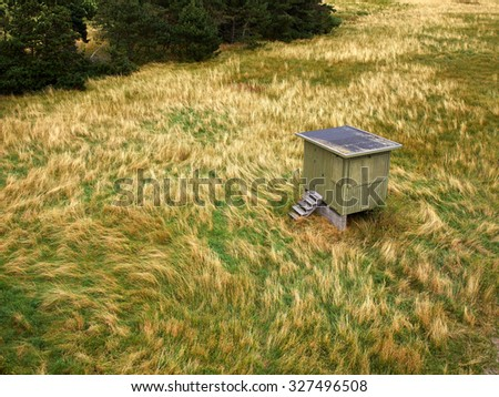 Small rural wooden shed house on the grass by the ocean - stock photo