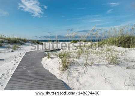 Small rustic boardwalk footpath through snow white sand dunes at a pristine Florida beach. - stock photo