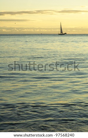 Small sail boat at cruising by sunset - stock photo