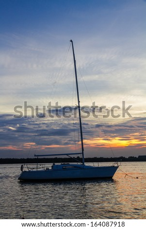 Small sailboat and wide river in twilight time  - stock photo