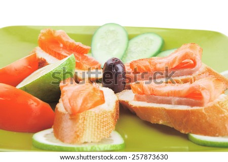 small salmon sandwich on green plate over white - stock photo
