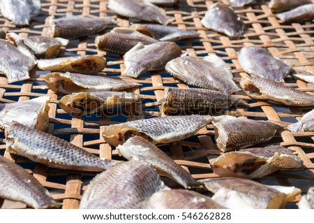 small salted fish drying under the sun in a basket