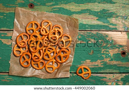 Small salted pretzels on old wooden background, top view  - stock photo