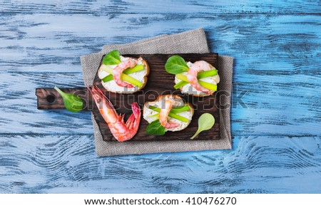 Small sandwiches bruschetta with ricotta cheese, shrimp, green onions, salad on wooden surface, top view, empty place for text - stock photo
