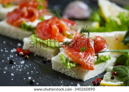 Small sandwiches canapes with salty salmon,  soft cheese and green salad, selective focus and shallow depth of field - stock photo