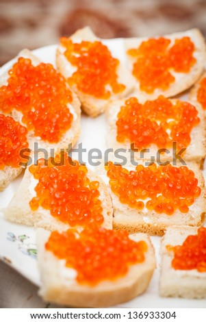 Small sandwiches with red caviar on a plate