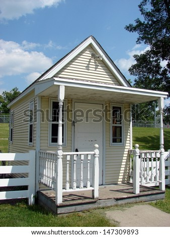 small scale yellow house with picket fence