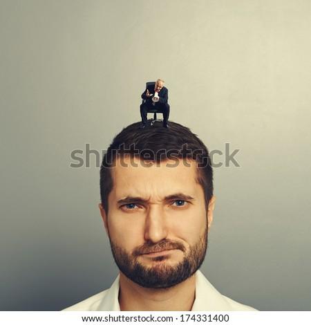 small senior man with megaphone screaming at big man - stock photo