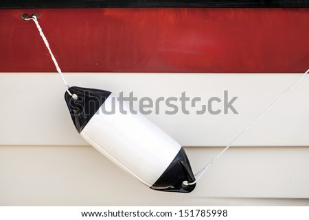Small ship bump element hanging above white and red yacht hull - stock photo