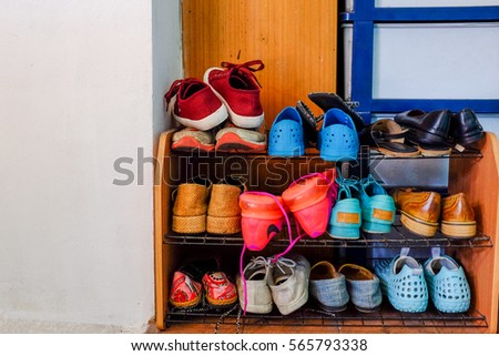 small shoe rack fully filled with many kinds of shoes sneakers and sandals too