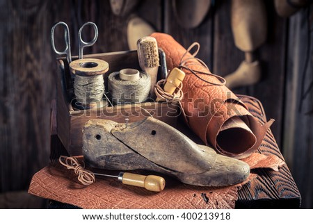 Small shoemaker workshop with shoes, laces and tools - stock photo