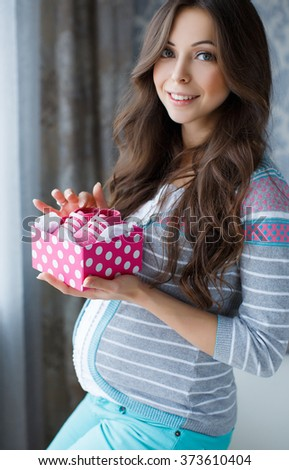 Small shoes for the unborn baby in the belly of pregnant woman. Pregnant woman holding small baby shoes relaxing at home in bedroom. Small shoes for the unborn baby in the belly of pregnant woman - stock photo