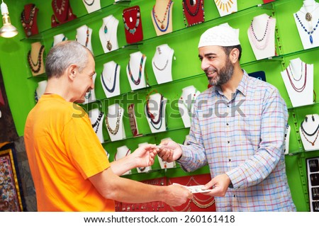 small shop owner indian man selling shawls, clothing and souvenirs at his store - stock photo