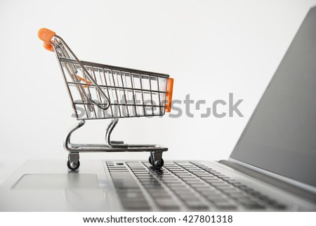 Small Shopping Cart On Laptop keyboard With Copy space. Isolated on gray background. Online Shopping Concept - stock photo