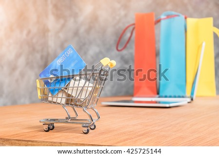 small shopping cart  with credit card inside and background with laptop and shopping bag - stock photo