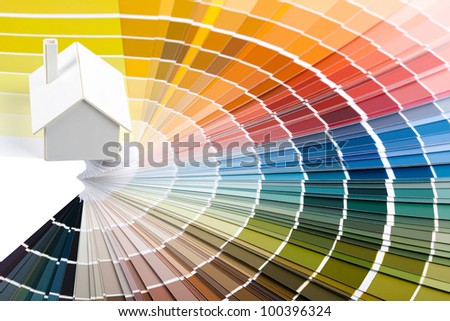 Small simple white model house on a color palette. - stock photo