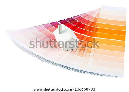 Small simple white model house on a color palette with different colors of orange spectrum. - stock photo