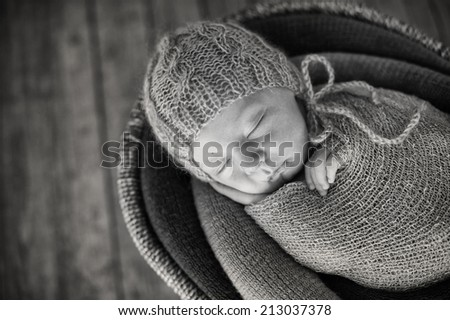 Small Sleeping Newborn Baby in Basket on Wooden Floor - black and white