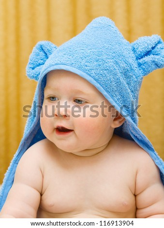 Small smiling baby in blue towel on bed - stock photo