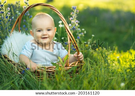 small smiling child in sliders sitting a basket on the grass - stock photo