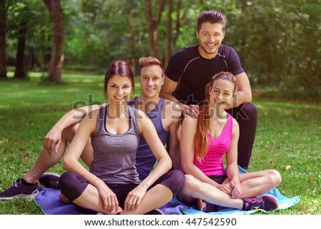 Small smiling group of athletes sits together on a blanket in the grass near the forest on a sunny day - stock photo