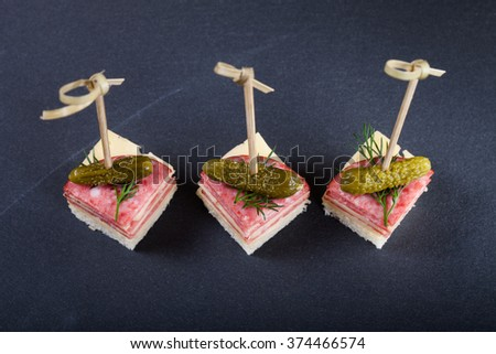 Small snacks canape with salami, cheese and pickle on skewer on a black slate plate. Selective focus. - stock photo