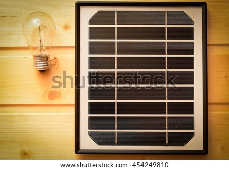 small solar panel and a light bulb. The concept of green energy. - stock photo