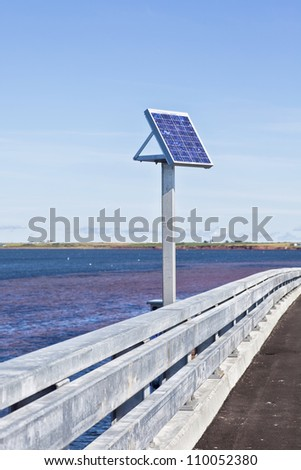 Small solar panel on the side of a bridge. - stock photo