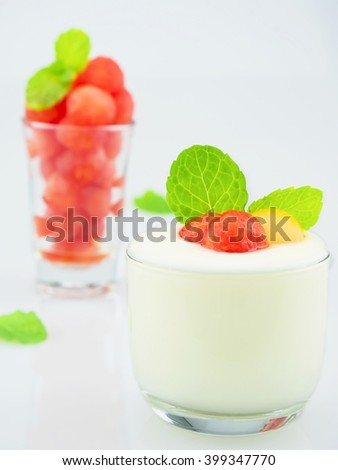 Small sphere shape of cantaloupe and watermelon in a glass with yogurt and mint over white background