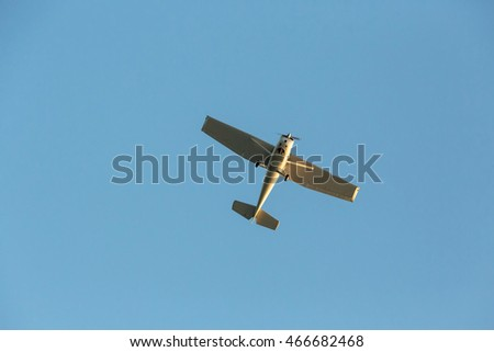 Small sport airplane flying in the background of blue sky, view from below, clear blue sky in background