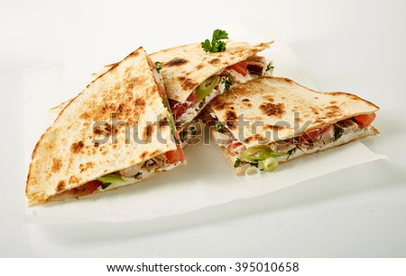 Small stack of cooked wheat tortilla quesadillas parts stuffed with onion, tomato and herbs in wax paper on white background - stock photo