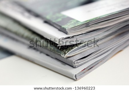 small stack of magazines on white backgound
