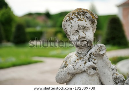 Small statue angel from stone in the gardens - stock photo