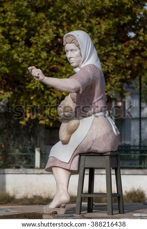 Small statue of a working lady on a roundabout on Portimao city, Portugal.