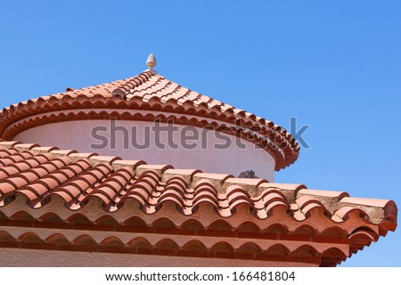 Small statue of an egg on the red tiled roof - stock photo