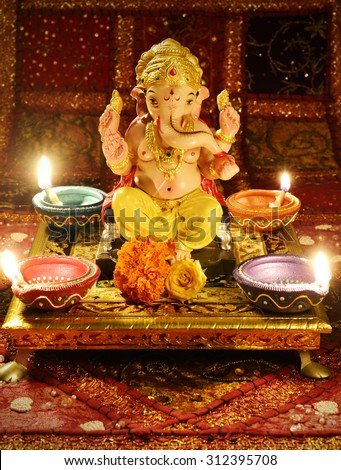 Small statue of Lord Ganesha. Pooja arrangement at home during Ganesh Festival in India. - stock photo