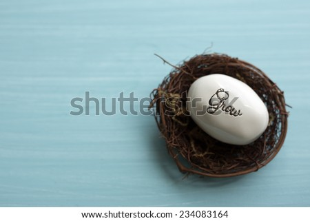 """Small stone with the word """"grow"""" in black script resting in a small nest on a turquoise wood background.  - stock photo"""