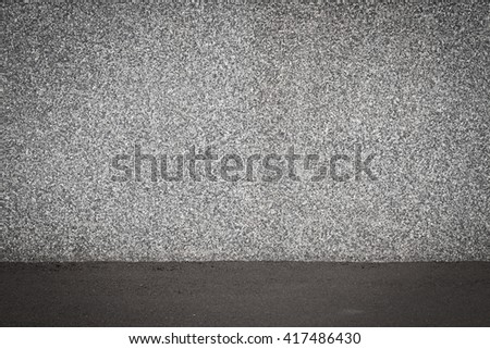 Small stones wall used for background texture with asphalt floor - stock photo