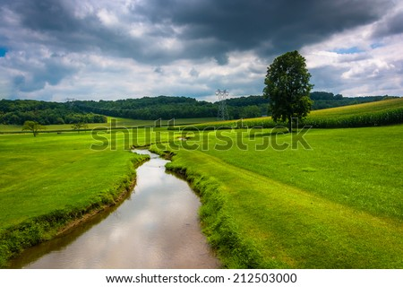 Small stream in a farm field in rural Carroll County, Maryland. - stock photo