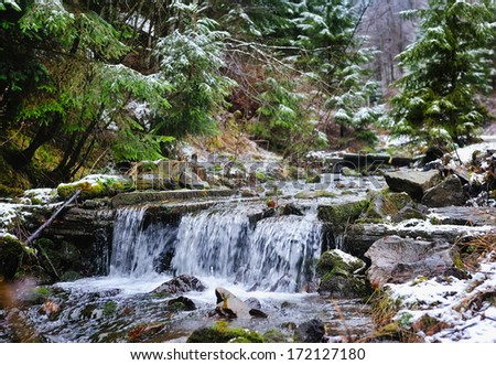 Small stream in mountains winter forest - stock photo